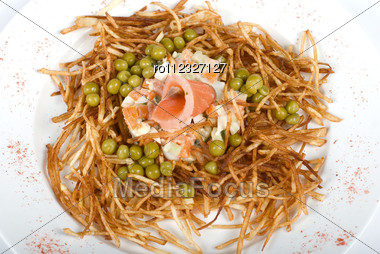 Closeup Of Salad With Salmon Fish At Fried Sliced Potato With Carrot And Peas Dressed By Tomato Sauce With Cognac Stock Photo