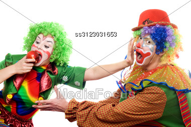 Clowns Are Fighting For An Apple. Stock Photo