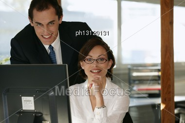 Co-workers In Front Of Desktop Computer Stock Photo