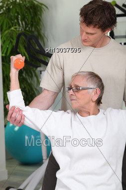 Coach Helping Senior Lady To Do Exercises Stock Photo