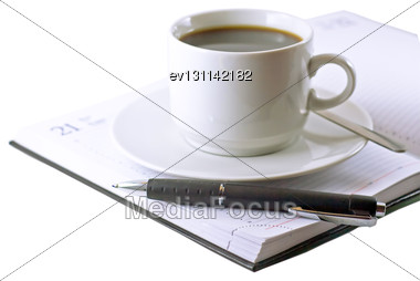 Coffee Cup, Standing On The Opened Daily Organizer . Isolated Stock Photo