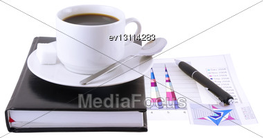 Coffee Cup, Standing On The Personal Organizer, On A Back Background-financial Diagrams . Isolated Stock Photo