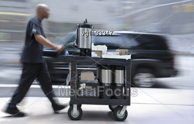 Coffee Delivery Man With Coffee Stainless Steel Containers Or Titans On A Cart Moving On A Sidewalk Motion Blur, Suv At Background Stock Photo