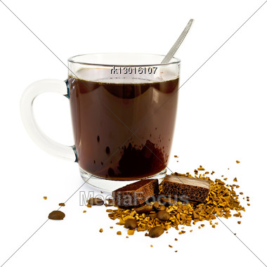 Coffee In A Glass Mug, A Spoon, Grains And Granules Of Coffee On The Table With A Dark Porous Chocolate Stock Photo