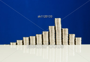 Coins Stacked In Bars Against Blue Background - Market Grouth Concept Stock Photo
