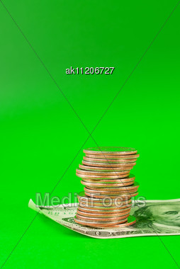 Coins Stacked In Bars Laying On 100 Dollar Bill Over Green Background Stock Photo