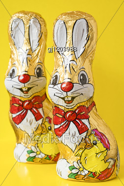 Colorful Chocolate Easter Bunnies, Isolated Over Yellow Stock Photo