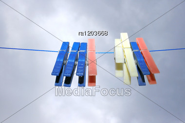 Colorful Clothespins With Rain Drops On The Rope On The Sky Background. Stock Photo