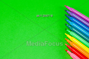 Colorful Felt Pens Over Green Background Stock Photo