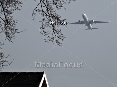 Commercial Jet Airplane Over Tree And Roof Against Clear Blue . Stock Photo