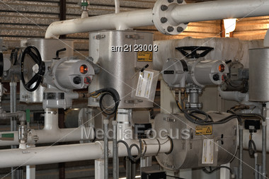 Commercial Oil Metering Valve In The Foreground With Electric. Stock Photo