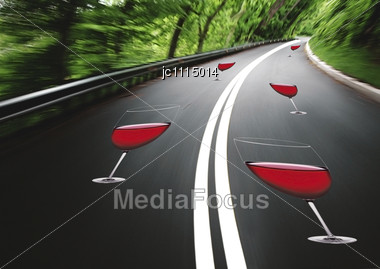 Concept Of Danger Of Drinking And Driving With Glasses Of Red Wine On A Winding Road With A Blurred Vision Stock Photo