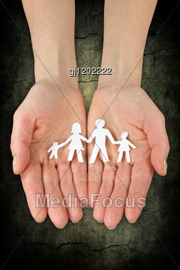 Concept For Security And Care. Hands With Paper Chain Of Family Stock Photo
