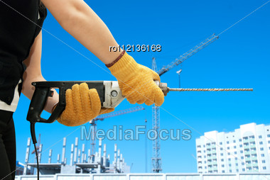 Construction Worker Building With Drill On A Building Background Stock Photo