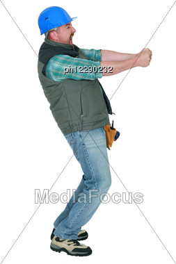 Construction Worker Pulling Something Stock Photo