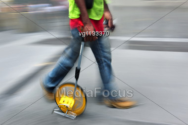 Construction Worker Walking On The Street Blurred Motion Carrying Measuring Wheel Equipment And Tools Stock Photo
