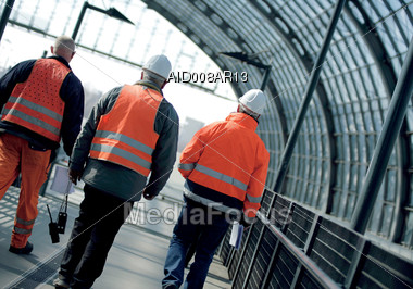 Construction Workers Wearing Safety Vests, Walking Away From Camera Stock Photo