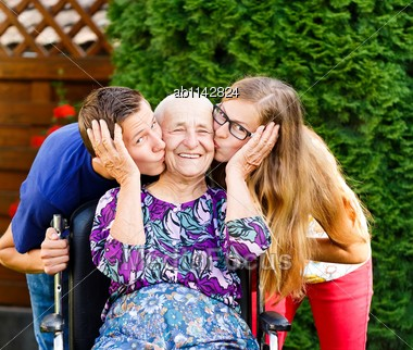 Contented Grandmother Being Loved And Kissed By Beautiful Grandchildren Stock Photo