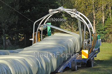 Continuous Wrapper At Work On Square Bales Of Hay, West Coast, New Zealand Stock Photo