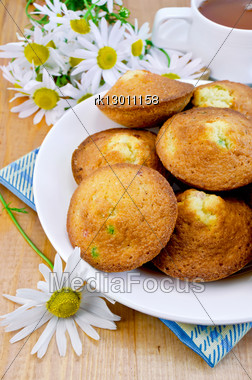 Cookies With Candied Fruit On A Plate, Blue And Yellow Plaid Cloth, White Cup Of Tea, Chamomile Against A Wooden Board Stock Photo
