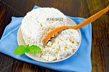 Cottage Cheese In A Bowl With Basil And A Wooden Spoon On Blue Napkin On The Background Of Wooden Boards Stock Photo