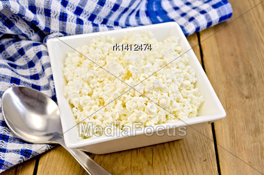 Cottage Cheese In A White Square Bowl, Blue Checkered Napkin, Spoon On A Wooden Board Stock Photo