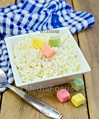 Cottage Cheese In A White Square Bowl With Colored Sugar Cubes, Blue Checkered Napkin, Spoon On A Background Of Wooden Boards Stock Photo