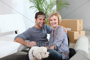 Couple And Dog Move Into Home Stock Photo