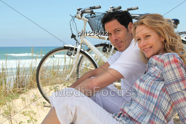Couple With Bikes Sitting On The Sand Dunes Stock Photo
