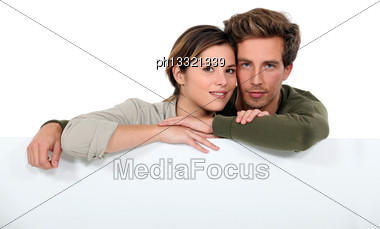 Couple With A Board Left Blank For Your Message Stock Photo