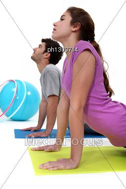 Couple Doing Yoga On Mat Stock Photo