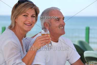 Couple Drinking Beer In Beach Terrace Stock Photo