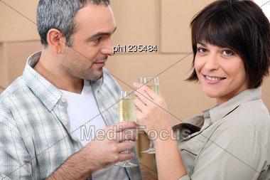 Couple Drinking Champagne In Front Of A Pile Of Cardboard Boxes Stock Photo