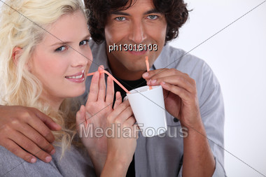 Couple Drinking From The Same Cup Stock Photo