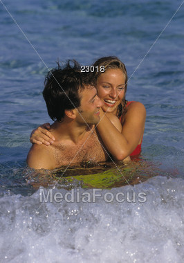 Couple embracing in the waves at the beach Stock Photo