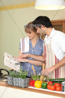 Couple Following A Recipe Book Stock Photo