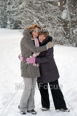 Couple Of Friends Having Fun On Winters Day In Forest. Stock Photo