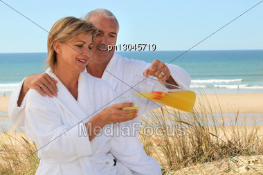 Couple In Bathrobes On The Beach Stock Photo