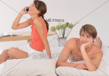 Couple In Bed & Woman Talking On Phone Stock Photo