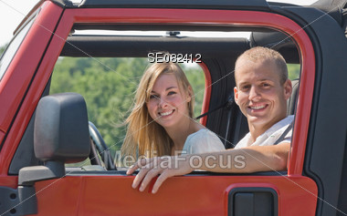 Couple in Red Jeep Stock Photo