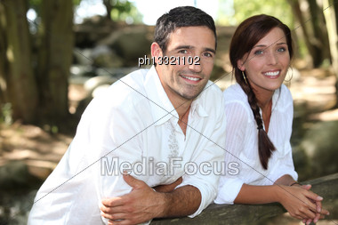 Couple In White Leaning On A Wooden Fence Stock Photo