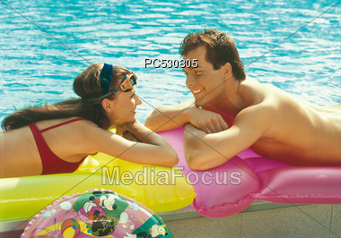 Couple Laying On Air Mattress By Pool Stock Photo