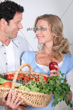 Couple Looking Into Each Other's Eyes With Vegetable Basket. Stock Photo