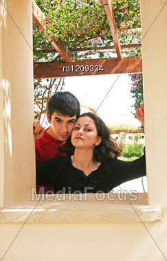 Couple In Love Looking From Wall Frame. Stock Photo