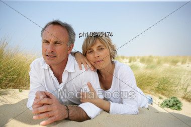 Couple Lying In A Sand Dune Stock Photo