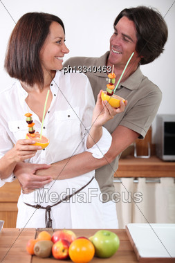 Couple Making Fruit Skewers Stock Photo
