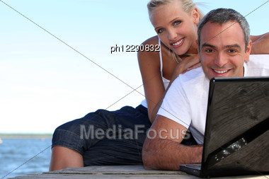 Couple On A Pontoon Near The Sea, The Man Is Doing Computer Stock Photo