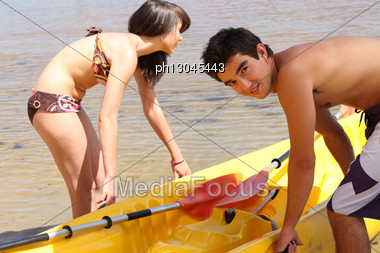 Couple Pulling Their Kayak Out Of The Water Stock Photo