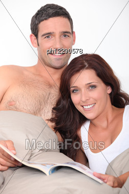 Couple Reading A Book In Bed Stock Photo