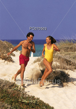 A couple running on the beach sand Stock Photo